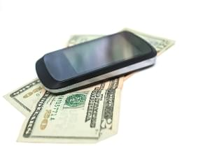 smartphone over heap of dollar on white