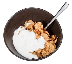 top view of yoghurt and spoon into bowl of cereal isolated on white background