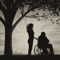 Silhouette of nurse caring for a disabled person in a wheelchair resting under a tree near sea