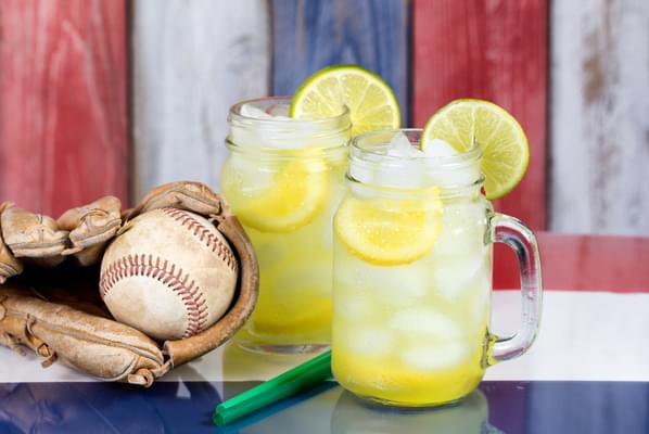 Glass jars filled with cold lemonade and baseball mitt with ball