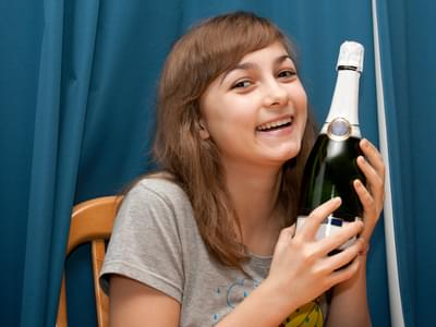 Girl with bottle champaign smiles