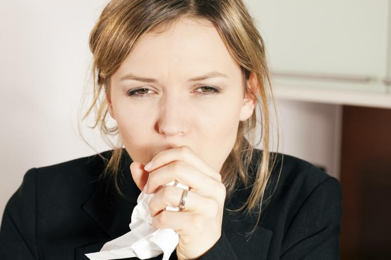 Woman having a cold, coughing, holding a handkerchief in front of her face