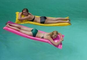 smiling girls lying on pool raft