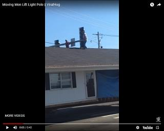 Moving Company Workers Lift Stop Light So Hauled House Can Get Through