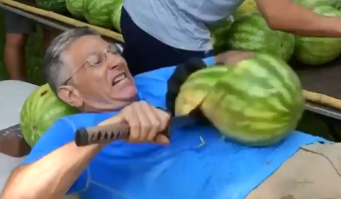 Man Chopping Watermelon On His Stomach