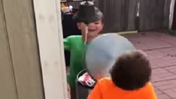 Two Boys Take Turns Hitting Each Other With Trash Lid