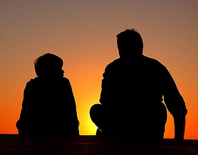 A child and dad silhouetted by sunset.
