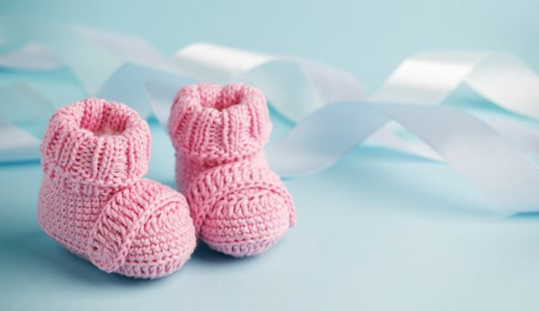 Pink Baby knitted shoes for newborns on blue background, Minimal