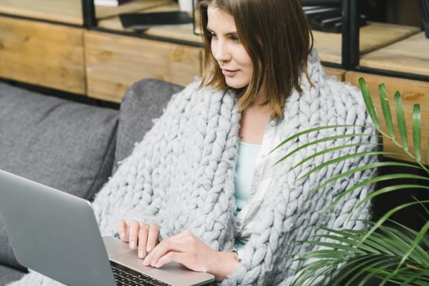 lovely-woman-in-blanket-browsing-laptop_23-21478019841