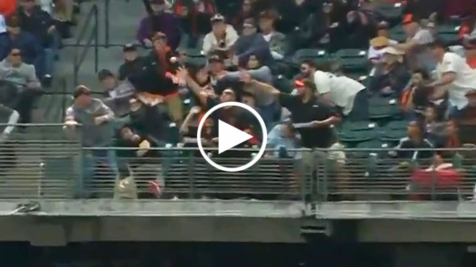 Fan bare-hands foul ball while holding nachos