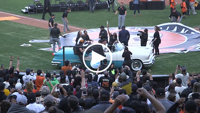 Bonds signs and throws balls, takes lap around field in vintage car after number retirement