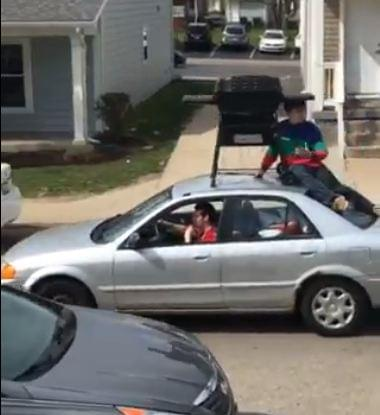 Guy riding on top of car with his grill gets scolded by police