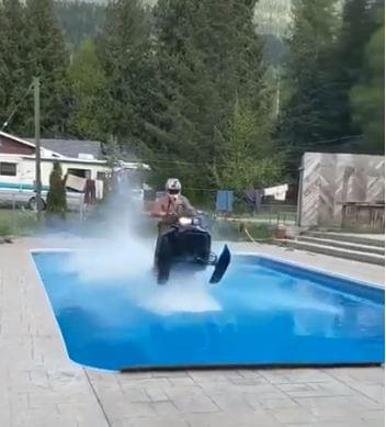 Guy attempts to cross pool with snowmobile
